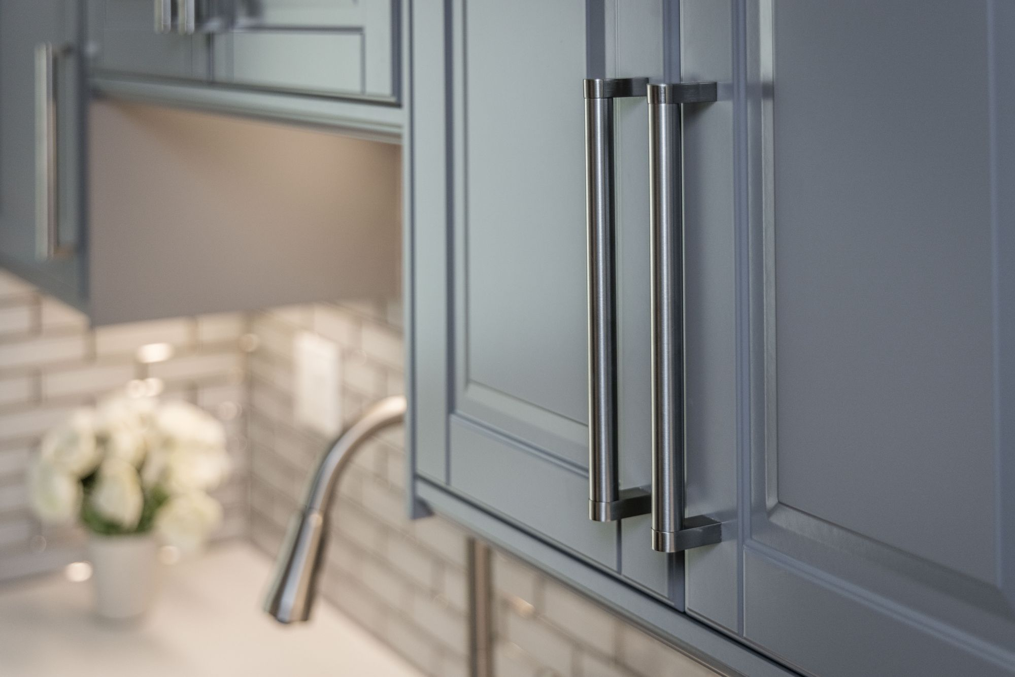 Kitchen cabinet with faucet and sink in background